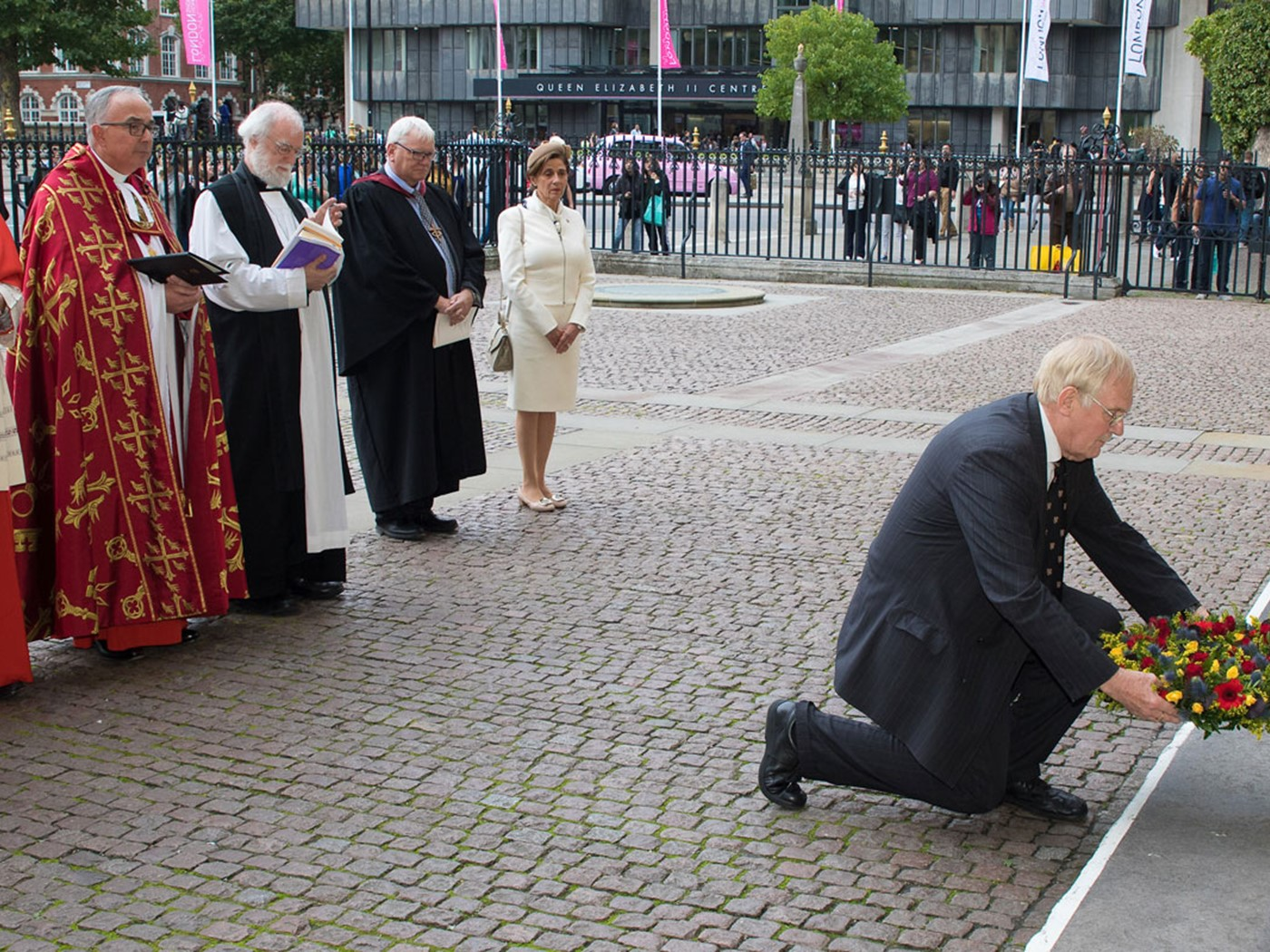 Julian Filochowski, Chair, Archbishop Romero Trust, lays a wreath beneath the statue of Blessed Oscar Romero's on the West front of the Abbey Church