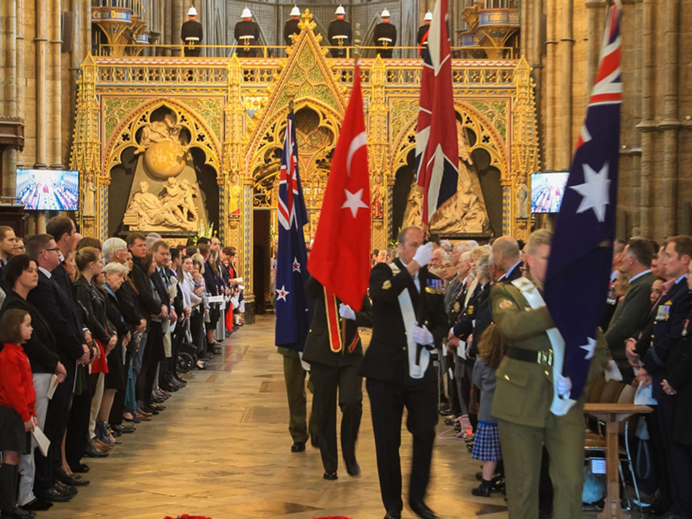 The flags of Australia, the United Kingdon, Turkey and New Zealand are borne through the Abbey Church